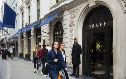 Shoppers walk past the Graff store