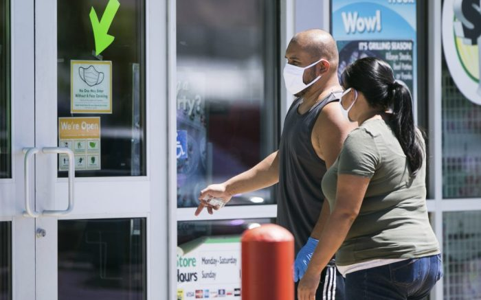 A mandatory face protection sign hangs on a window of the Dollar Tree as T.J. George, left, and Roberta George walk toward the front entrance Monday, June 22, 2020, in Yakima, Wash. Washington state will require people to wear facial coverings in most indoor and outdoor public settings, under a statewide public health order announced Tuesday by Gov. Jay Inslee in response to ongoing COVID-related health concerns. (Amanda Ray / Yakima Herald-Republic via AP)