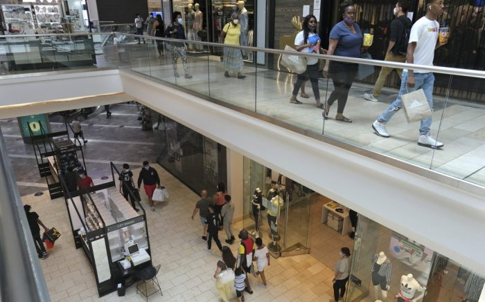 Shoppers walk around Garden State Plaza in Paramus, N.J., Monday, June 29, 2020. New Jersey's indoor shopping malls reopened Monday from their COVID-19 pause. Democratic Gov. Phil Murphy set the date earlier this month after he shuttered many sectors of the state's economy because of the outbreak. (AP Photo/Seth Wenig)