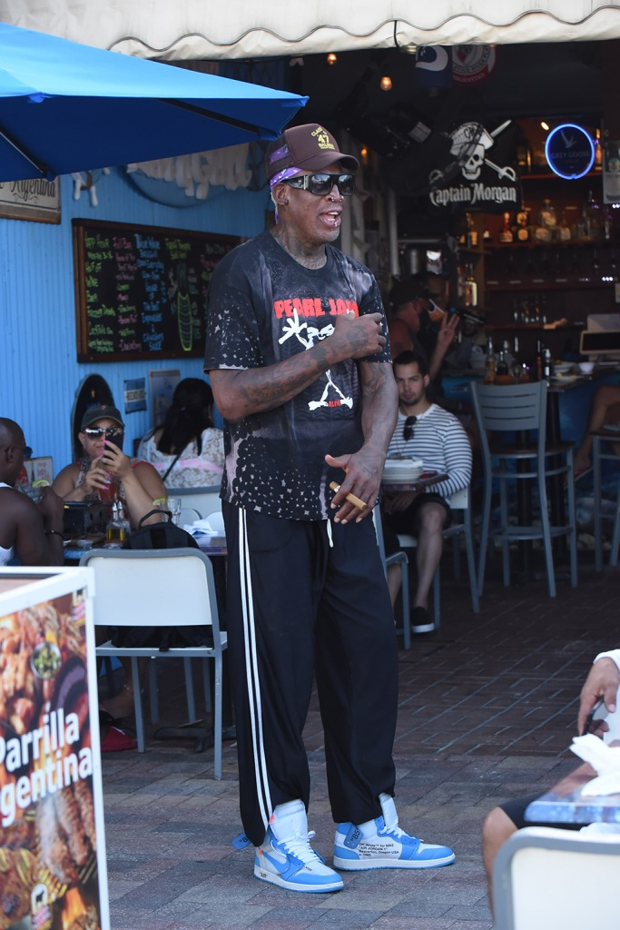 dennis rodman, off-white x nike sneakers, off-white jordans, unc jordans, track pants, baseball cap, NBA legend Dennis Rodman parties on the busy Hollywood Beach Boardwalk with no masks or social distancing as Florida's Covid cases soar. The former basketball ace was spotted kicking back on Sunday Funday (july 19) with bikini clad galpal seemingly without a care in the world despite the raging virus. he was seen taking selfies with approaching fans - young and old - and enjoying outside dining with his group. Broward County is now under nightly curfew after an emergency order was issued amid record highs in the state. Florida reported more than 12,400 new cases Sunday, bringing its total to more than 350,000.Pictured: Dennis RodmanRef: SPL5177860 200720 NON-EXCLUSIVEPicture by: Michele Eve Sandberg / SplashNews.comSplash News and PicturesUSA: +1 310-525-5808London: +44 (0)20 8126 1009Berlin: +49 175 3764 166photodesk@splashnews.comWorld Rights