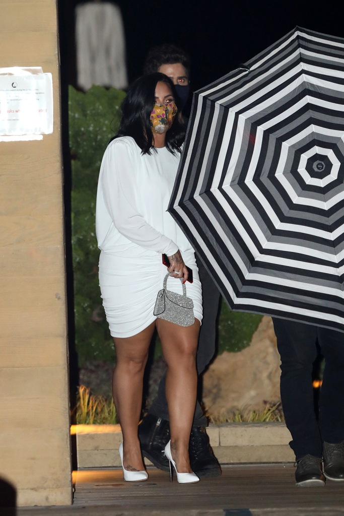 Demi Lovato, white minidress, heels, legs, by far bag, engaged, face mask, and Max Ehrich celebrate their engagement by having dinner at Nobu Malibu in Malibu. Demi Lovato just recently got engaged to Max Ehrich on the beach in Malibu, then afterwards the due had a three hour celebration at the Japanese restaurant. 23 Jul 2020 Pictured: Demi Lovato and Max Ehrich. Photo credit: Photographer Group/MEGA TheMegaAgency.com +1 888 505 6342 (Mega Agency TagID: MEGA690352_003.jpg) [Photo via Mega Agency]
