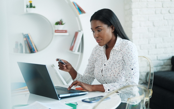 Black woman paying online purchase with credit card after shopping. African american people with laptop computer using card for internet transaction at home