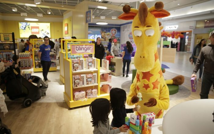"In this Dec. 9, 2019, photo the Toys R Us mascot, Geoffrey, plays with twins Damon, left, and Logan Ramirez at the new store at a mall in Paramus, N.J. To get shoppers to spend more on toys, stores want them to spend time first. Toys R Us opened its first two ""experiential"" stores under new ownership that features a tree fort that kids climb up and an interactive mirror. (AP Photo/Seth Wenig)"