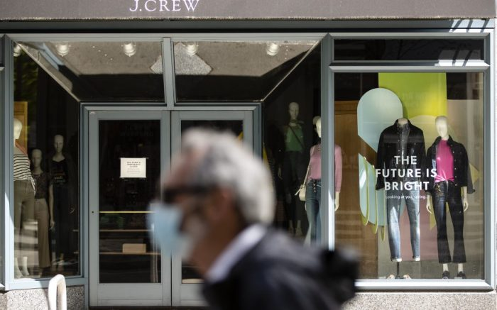 A person wearing a protective face mask as a precaution against the coronavirus walks past a shuttered J. Crew storefront in Philadelphia, Monday, May 4, 2020. The parent company of clothing chain J. Crew has filed for Chapter 11 bankruptcy, yet another casualty of the coronavirus pandemic that is wreaking havoc on the retail world. Retail veteran Mickey Drexler led J. Crew for more than a decade, helping it become a coveted fashion brand before it hit a multi-year sales slump. (AP Photo/Matt Rourke)