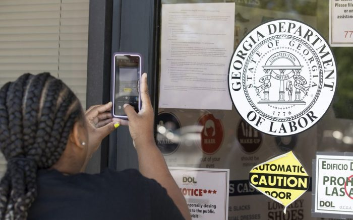 Arnashia McCain uses her phone to copy phone numbers posted on the locked doors of a Georgia Department of Labor office Thursday, May 7, 2020, in Norcross Ga. McCain, who said she drives for Lyft and has had her hours cut in her job in retail, has been unable check on the status of her her unemployment claim. (AP Photo/John Bazemore)