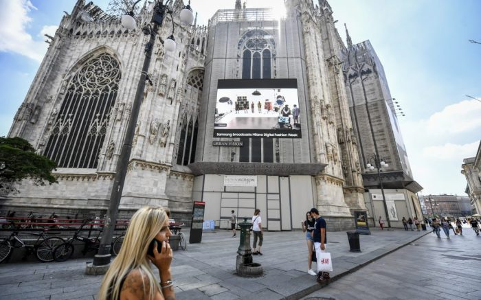 Pedestrians pass by a screen hanging on the side of the Duomo gothic cathedral and showing a Versace model, during the Milan Digital Fashion Week, in Milan, Italy, Thursday, July 16, 2020. Forty fashion houses are presenting previews of menswear looks for next spring and summer and pre-collections for women in digital formats, due to concerns generated by the COVID-19. (Claudio Furlan/LaPresse via AP)