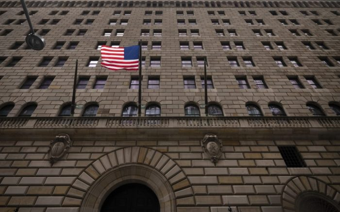 The United States flag hangs on the Federal Reserve Bank of New York, Tuesday, Aug. 4, 2020. (AP Photo/Mark Lennihan)