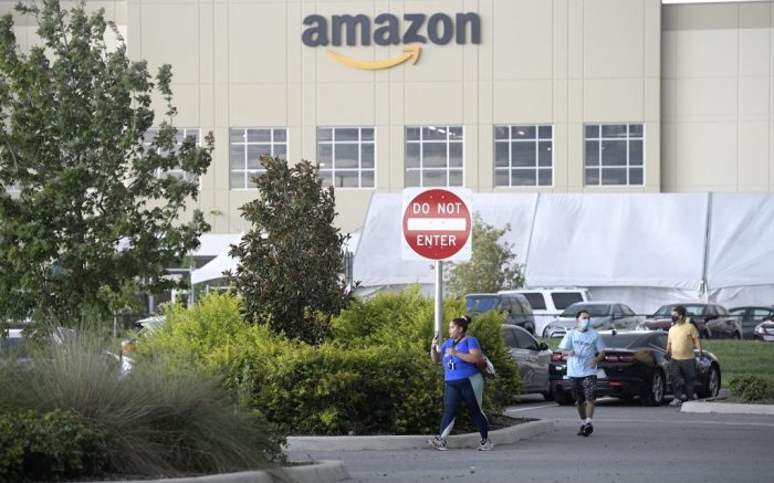 Employees leave the Amazon Lake Nona Fulfillment Center, Sunday, Aug. 9, 2020, in Orlando, Fla. Many beaches and businesses have reopened during the new coronavirus pandemic. (Phelan M. Ebenhack via AP)