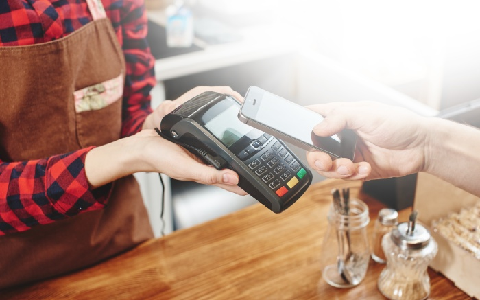 Woman paying by smartphone using contactless payments