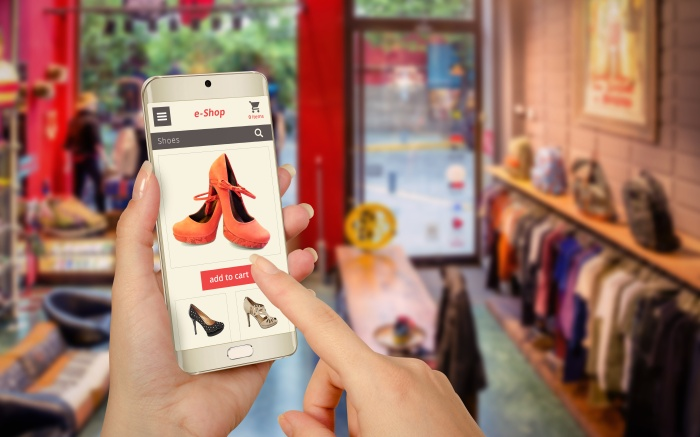 hand holding smartphone to buy shoes online while in store