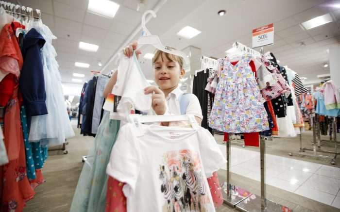 "IMAGE DISTRIBUTED FOR MACY'S - Kimberly Rosas, 6, shops for back to school clothes during a private, in-store ""Shop with a Cop"" experience on Friday, August 9, 2019 in Dallas, Texas. Through a corporate partnership with Catholic Charities Dallas and $2,500 donation, 10 students were provided a $250 Macy's gift card to buy back to school clothes. (Brandon Wade/AP Images for Macy's)"