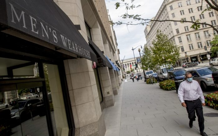 A man walks past a closed and empty Men's Wearhouse in Washington, Monday, Aug. 3, 2020. Tailored Brands, known for its clothing chains Men's Wearhouse and JoS. A. Bank, struggled as the pandemic shut stores and consumer demand for office attire dropped, has filed for bankruptcy. (AP Photo/Andrew Harnik)