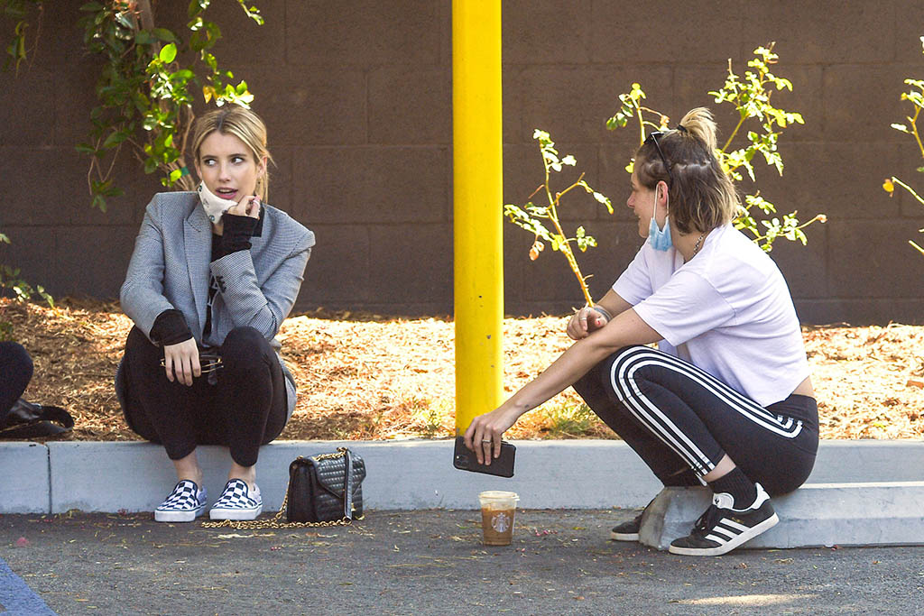 EXCLUSIVE: Pregnant Emma Roberts steps out for coffee with Kristen Stewart. The pair, who were also joined by two other friends, were seen stopping by a local Starbucks and stopped in the parking lot to chat. Emma was all smiles and kept her baby bump hidden under a heavy coat despite it being a pretty warm day out. 30 Aug 2020 Pictured: Emma Roberts and Kristen Stewart. Photo credit: Marksman/Snorlax/MEGA TheMegaAgency.com +1 888 505 6342 (Mega Agency TagID: MEGA697392_001.jpg) [Photo via Mega Agency]