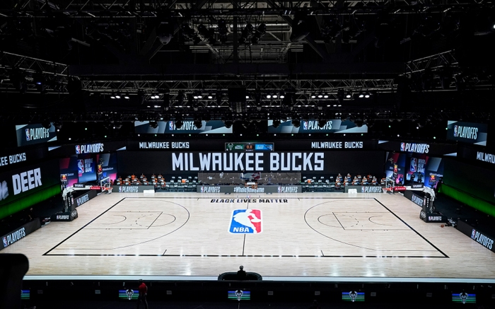 The court and benches are empty of players and coaches at the scheduled start of an NBA basketball first round playoff game between the Milwaukee Bucks and the Orlando Magic, Wednesday, Aug. 26, 2020, in Lake Buena Vista, Fla. (AP Photo/Ashley Landis, Pool)