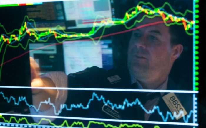 Specialist Michael McDonnell is reflected in a screen at his post on the floor of the New York Stock Exchange, Friday, March 20, 2015. Stocks advanced Friday, capping a strong week, helped by a recovery in the price of oil and earnings from Olive Garden owner Darden Restaurants and sportswear giant Nike. The Nasdaq composite index inched closer to its all-time high set at the height of the dot-com bubble. (AP Photo/Richard Drew)