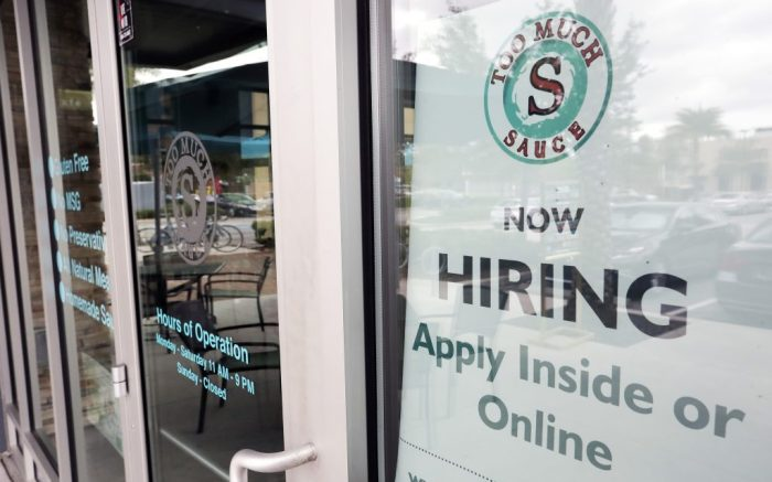 FILE - In this Nov. 4, 2019 file photo a job posting is displayed near the entrance outside a restaurant in Orlando, Fla.  The number of Americans filing new claims for unemployment insurance fell last week for a second straight week, an indication that the coronavirus has not yet hit the labor market in a major way. The Labor Department said Thursday, March 12, 2020, that applications for unemployment benefits, a good proxy for layoffs, dropped by 4,000 last week to a seasonally adjusted 211,000. Claims had fallen by 4,000 in the previous week as well. (AP Photo/John Raoux)