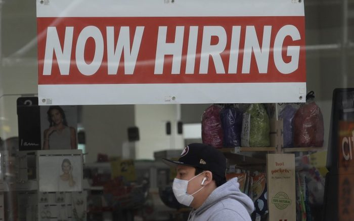 FILE - This May 7, 2020, file photo shows a man wearing a mask while walking under a Now Hiring sign at a CVS Pharmacy during the coronavirus outbreak in San Francisco. California's unemployment rate nearly tripled in April because of the economic fallout from coronavirus pandemic. (AP Photo/Jeff Chiu, File)