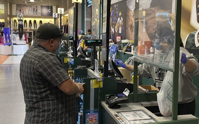 A customer makes a purchase at Dick's Sporting Goods store at the Los Cerritos Center mall amid the global coronavirus COVID-19 pandemic, Saturday, May 30, 2020, in Cerritos, Calif. (Kirby Lee via AP)
