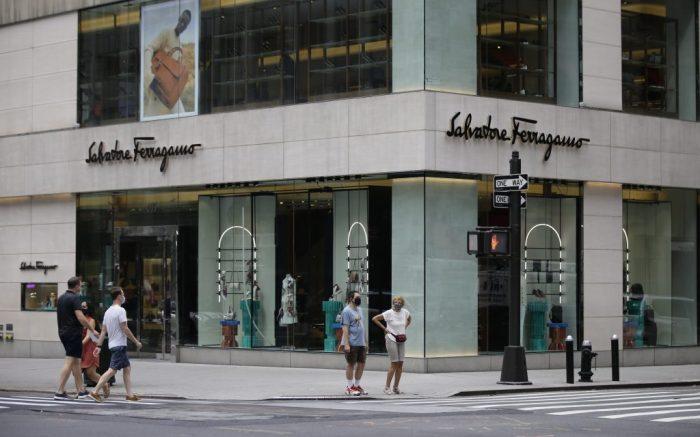 Pedestrians wearing protective masks walk past a Salvatore Ferragamo location Wednesday, July 8, 2020, in New York. (AP Photo/Frank Franklin II)