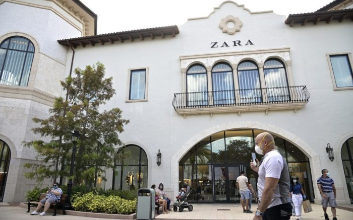Visitors wear masks as they walk past a Zara store at the Disney Springs shopping, dining and entertainment complex, Saturday, Aug. 1, 2020, in Lake Buena Vista, Fla. Disney Springs reopened as part of a phased reopening during a new coronavirus pandemic, which included limited parking and entrances, temperature screenings prior to entry, face coverings required for guests ages 2 and up and social distancing. (Phelan M. Ebenhack via AP)