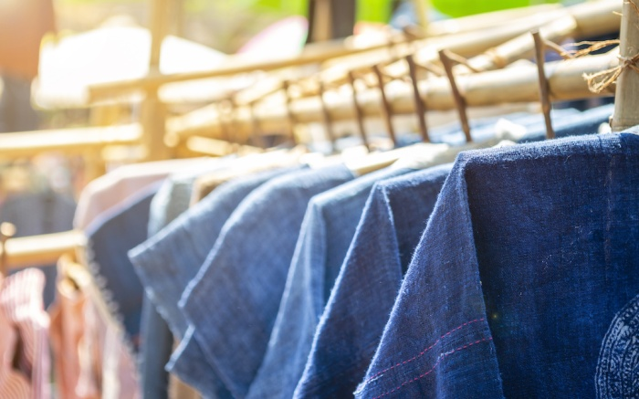 Blue cotton shirt haning on the bamboo rail, outday day light, shopping and fashion concept, Thai style blue cotton shirt