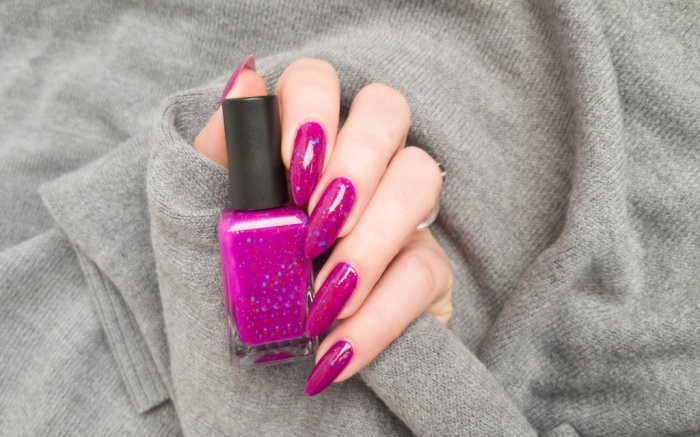 Female hand with long nails and pink fuchsia bottle manicure with nail polish
