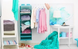 Fashionable clothes hanging on rack at