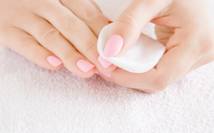Woman hand removing pink nail polish with white cotton pad on white towel. Front view. Close up.