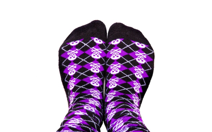 Fun purple and black socks with skulls on isolated white background