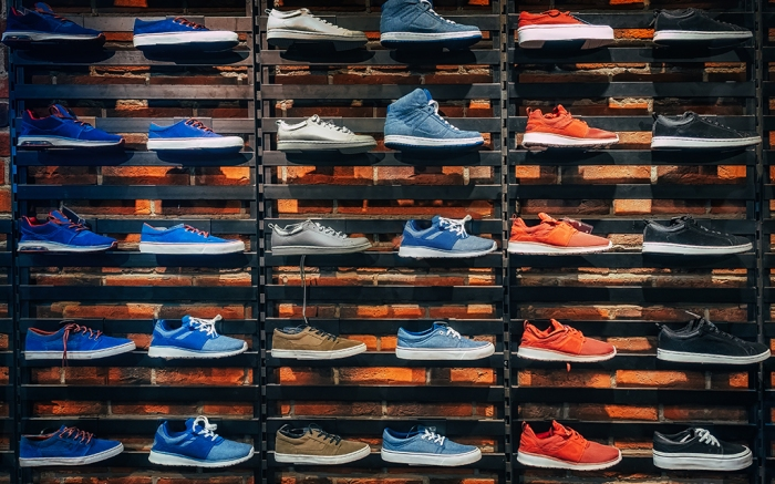 Lots of different sneakers on the showcase on market. Image of sport shoes on shop-window in a store