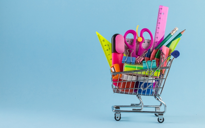 Shopping cart with different stationery on the light blue background. Back to school Education concept.Colorful school supplies in shopping cart