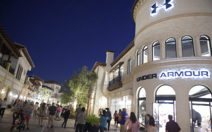 Guest walk past an Under Armour store in the Town Center neighborhood at Disney Springs in Lake Buena Vista, Fla., Sunday, May 15, 2016. (Phelan M. Ebenhack via AP)