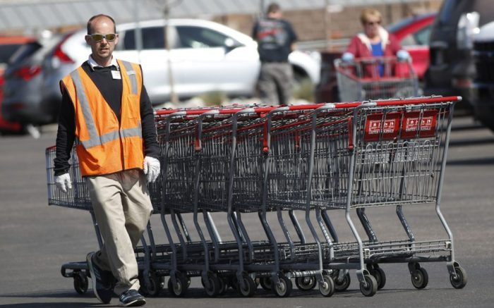 A Costco warehouse worker wears latex gloves as he collects carts in the parking lot as a statewide stay-at-home order takes effect to reduce the spread of the new coronavirus Thursday, March 26, 2020, in Arvada, Colo. (AP Photo/David Zalubowski)