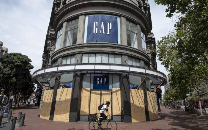 In this photo taken Friday, April 17, 2020, a man rides his bicycle past the boarded up and closed Gap store near Union Square in San Francisco. (AP Photo/Eric Risberg)