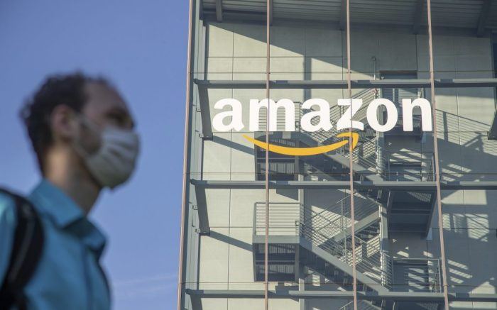 Ein junger Mann mit Maske vor dem Deutschlandsitz von Amazon in München. Die Aktie von Amazon hat seit dem Ausbruch des Corona Virus einen Höhenflug hingelegt. -- A young man is wearing a protective mask in front of the German Headquarters of Amazon. The stock of the online shopping giant and global tech company is experiencing an enourmous growth since the start of the covid-19 pandemic. (Photo by Alexander Pohl/Sipa USA)(Sipa via AP Images)