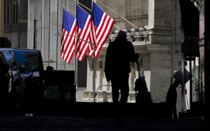 Pedestrians pass the New York Stock Exchange Wednesday, Oct. 14, 2020, in New York.  Stocks are slipping on Wall Street Wednesday as talks drag on in Washington over another economic stimulus package.(AP Photo/Frank Franklin II)