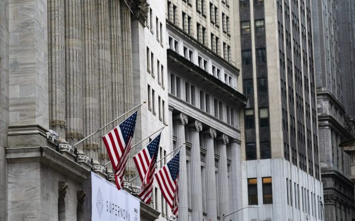 United States flags hang from the New York Stock Exchange, Monday, Oct. 26, 2020. Stocks are slumping in afternoon trading on Wall Street Monday and deepening last week's losses. (AP Photo/Mark Lennihan)