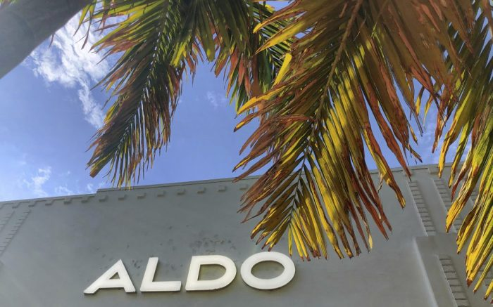 An Aldo retail shoe store logo is framed in a palm tree in the Lincoln Road district of Miami Beach, Florida, Thursday, June 6, 2019. The Aldo Group is a Canadian retailer that owns and operates a worldwide chain of shoe and accessories stores, founded by Aldo Bensadoun in Quebec in 1972 .(AP Photo/NewsBase)