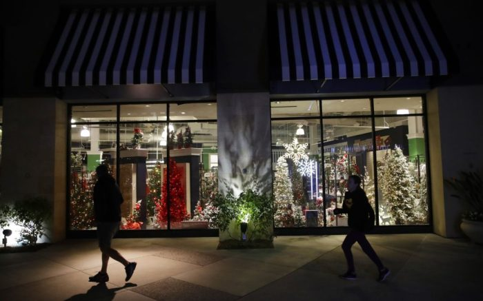 FILE - In this Dec. 16, 2019, file photo shoppers walk past a storefront with seasonal holiday products in Santa Clarita, Calif. Holiday shopping doesn't end with Christmas. Bargain hunters can take advantage of fatter discounts on clothing, home decor and other items between Christmas and well into January. (AP Photo/Marcio Jose Sanchez, File)