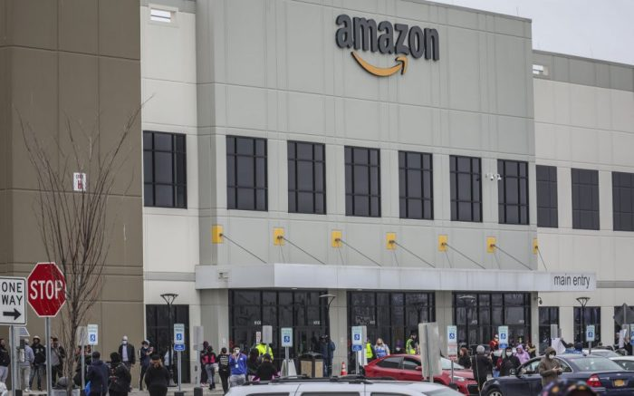 Workers at Amazon's fulfillment center in Staten Island, N.Y., gather outside to protest work conditions in the company's warehouse, Monday March 30, 2020, in New York. Workers say Amazon is not doing enough to to keep workers safe from the spread of COVID-19 and coronavirus. (AP Photo/Bebeto Matthews)