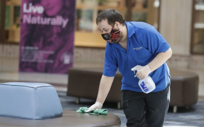 A worker disinfects a seat at SouthPark Mall, Wednesday, May 13, 2020, in Strongsville, Ohio. Ohio retail businesses reopened Tuesday following a nearly two-month-long shutdown ordered by Gov. Mike DeWine to limit the spread of the coronavirus. (AP Photo/Tony Dejak)