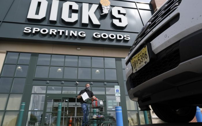 Gus Promollo delivers orders to customers waiting in their cars at Dick's Sporting Goods in Paramus, N.J., Monday, May 18, 2020. Nonessential businesses, shuttered because of the coronavirus outbreak, opened today for curbside pickup in New Jersey. Curbside pickup at businesses — like retail stores — and nonessential construction were able to start at 6 a.m. Monday under an executive order signed by Gov. Phil Murphy. (AP Photo/Seth Wenig)
