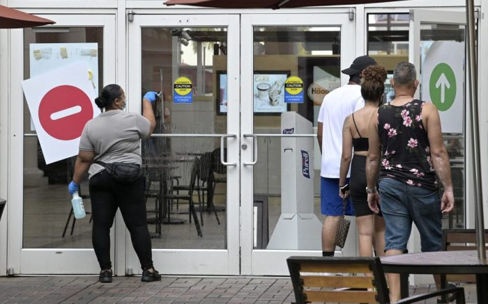 A mall employee cleans a door at the Orlando International Premium Outlets mall, Saturday, July 4, 2020, in Orlando, Fla. Many beaches and businesses have reopened during the new coronavirus pandemic. (Phelan M. Ebenhack via AP)