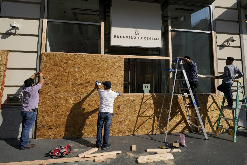 A work crew puts up wooden boards at a Brunello Cucinelli store in San Francisco, Sunday, Nov. 1, 2020, ahead of Election Day. (AP Photo/Jeff Chiu)