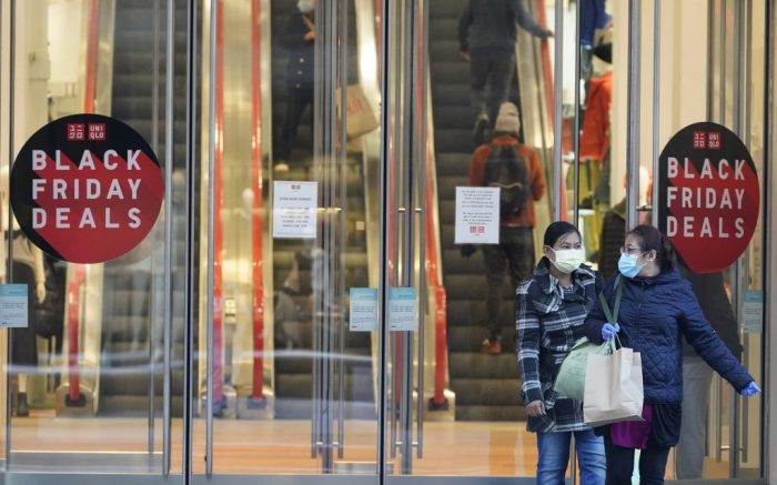 Black Friday shoppers wear face masks and gloves as the leave the Uniqlo store along Fifth Avenue, Friday, Nov. 27, 2020, in New York. (AP Photo/Mary Altaffer)