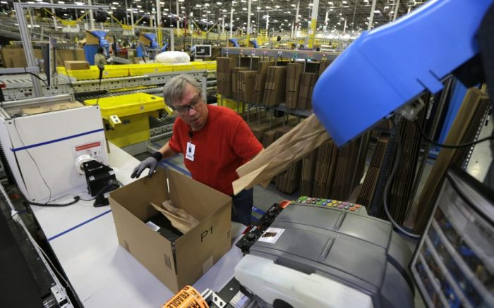 Mark Oldenburg packs a box for shipment to a customer, Monday, Nov. 30, 2015, at Amazon.com's fulfillment center in DuPont, Wash. (AP Photo/Ted S. Warren)