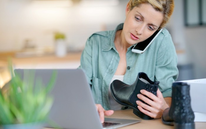 Woman holding up shoe purchased online while on phone to initiate an e-commerce return