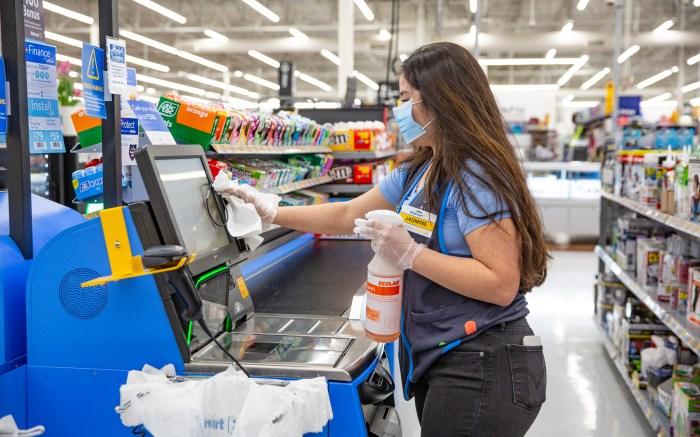 Walmart associate cleans self-checkout lane
