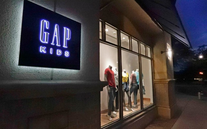 FILE - This Aug. 23, 2018, file photo shows a window display at a Gap Kids clothing store in Winter Park, Fla.  Gap is moving away from  the nation's malls. The brand, which was for decades a fixture at shopping malls around the country, said that it will be closing 220 stores _ or one third of its store base  by early 2024 _ and focus on outlet malls and its e-commerce business.   (AP Photo/John Raoux, File)