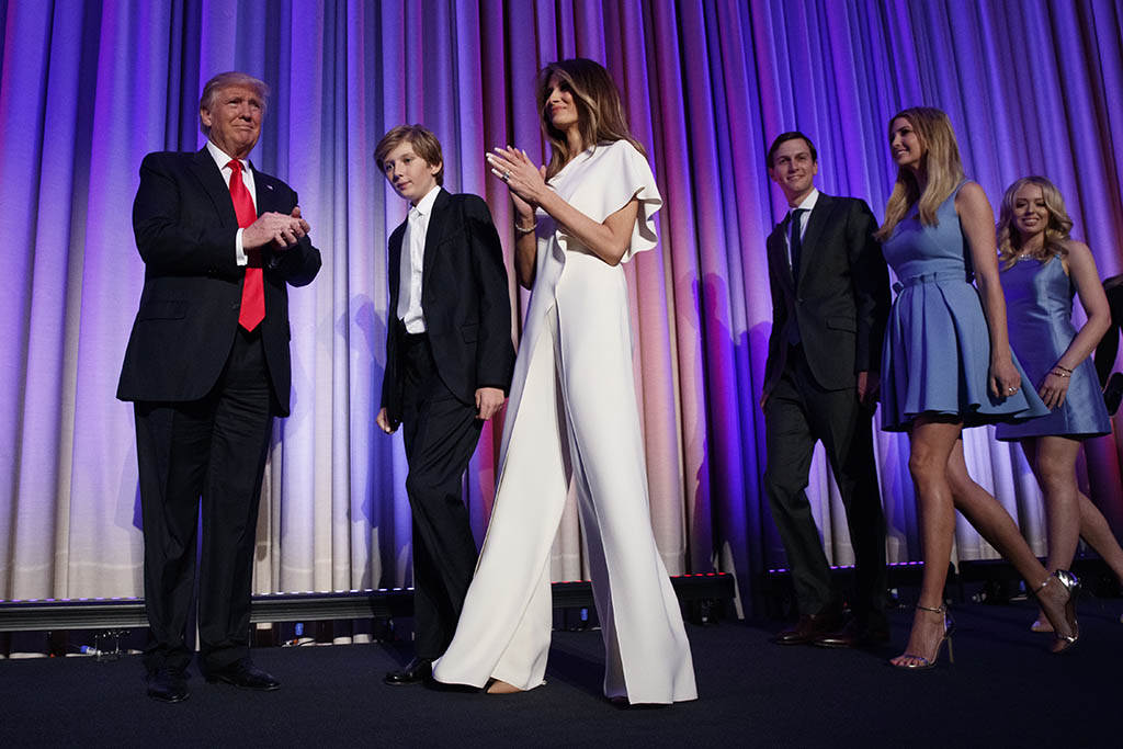 FILE - This Nov. 9, 2016 file photo shows Republican presidential candidate Donald Trump, left, arriving to speak to an election night rally in New York with his son Barron, from second left, wife Melania, son-in-law Jared Kushner and daughters Ivanka Trump and Tiffany Trump. New York City has lowered its cost estimate for guarding President Donald Trump, his family and their Manhattan residence. The original estimate of $35 million has been lowered to $24 million to guard the Trumps and Trump Tower during the 2½ months between Election Day and Inauguration Day. (AP Photo/ Evan Vucci, File)